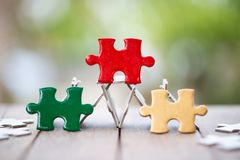 Piece of Red green and gold jigsaw puzzle On the old wood And green background. teamwork concept. symbol of association and. Connection. business strategy royalty free stock photography