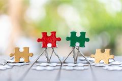 Piece of Red green and gold jigsaw puzzle On the old wood And green background. teamwork concept. symbol of association and. Connection. business strategy royalty free stock photos