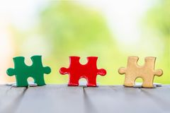 Piece of Red green and gold jigsaw puzzle On the old wood And green background. teamwork concept. symbol of association and stock photography