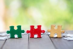Piece of Red green and gold jigsaw puzzle On the old wood. teamwork concept stock photography