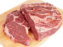 Piece of ribeye on cutting plank Stock Images