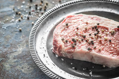 Piece of ribeye steak and peppercorn and salt on a plate of tin Stock Images