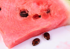 Piece of ripe watermelon with seeds on a white plate Stock Photography