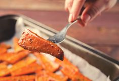 PIece of Roasted Caramelized organic Carrots with spices on fork in hand Stock Image