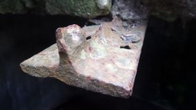Piece of rusty iron. Coming out from inside a rock in a cave royalty free stock photos