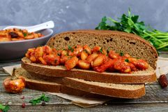 A piece of rye bread with beans. Stewed beans in tomato sauce with herbs and spices on the table. Royalty Free Stock Images