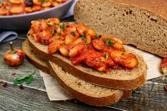 A piece of rye bread with beans. Stewed beans in tomato sauce with herbs and spices on the table. Stock Images