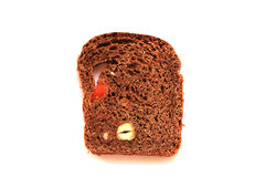 A piece of rye bread with nuts and dried apricots. The texture of the bread against the white background Stock Images