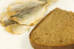 Piece of rye bread and three dried small fishes. On a white plate Royalty Free Stock Photo