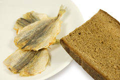 Piece of rye bread and three dried small fishes. On a white plate. On a white background Stock Images