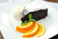 A piece of Sachertorte with ball of vanilla ice cream, three orange slices and mint spring Royalty Free Stock Image