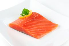 Salmon Fillet with Lemon and Parsley on Plate. A piece of salmon fillet with a lemon slice and parsley on a white plate Royalty Free Stock Images