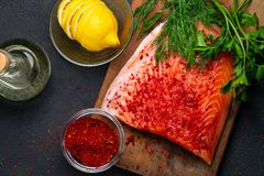 Piece of salmon fillet on a wooden cutting board with ingredients for its further preparation, top view - photo, image royalty free stock photography