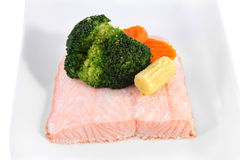 Piece of salmon on a plate, steamed, decorated with vegetables. Stock Image