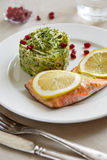 A piece of salmon and salad. Apiece of salmon decorated with lemon and a portion of vegetable salad royalty free stock photography