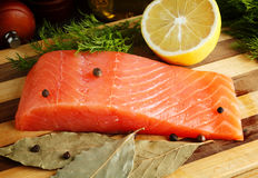 Piece of salmon with spices on cutting board. Close-up Royalty Free Stock Photos