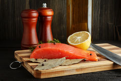 Piece of salmon with spices on cutting. Board closeup Stock Photo