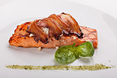 Piece of salmon steak with bacon. Royalty Free Stock Photos