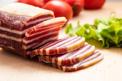 Piece of sausage with bacon Stock Images
