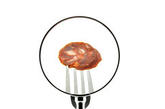 A piece of sausage on a fork punctured seen behind a magnifying glass. On a white background stock photo
