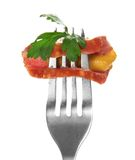Piece of sausage with greens and mustard on fork Stock Images