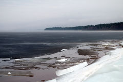 A piece of sea shore with breaking ice fore and misty coastline in the background. Baltic sea, spring in the north Stock Photo