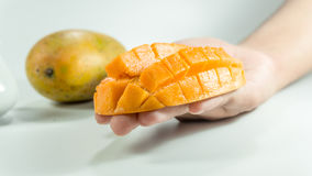 Sliced cube of fresh mango on hand. Piece of Sliced cube of fresh mango on hand. Asian fresh mango on white bachground stock photos