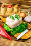 Piece and sliced fresh pork lard, fresh produce, greens, vegetables on the wooden board and knife on table. Stock Images
