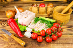 Piece and sliced fresh pork lard, fresh produce, greens, vegetables on the wooden board and knife on table. Royalty Free Stock Images