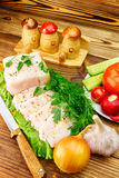 Piece and sliced fresh pork lard, fresh produce, greens, vegetables on the wooden board and knife on table. Royalty Free Stock Photos