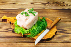 Piece and sliced fresh pork lard, fresh produce, greens on the wooden board and knife on table. Stock Image