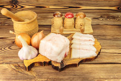 Piece and sliced fresh, raw pork lard on wooden board, mortar, garlic, onion on the table. Piece and sliced fresh, raw pork lard on wooden board, mortar, garlic Stock Photography