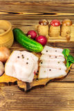 Piece and sliced fresh, raw pork lard on wooden board with vegetables, spices on the table. Piece and sliced fresh, raw pork lard on wooden board with Stock Photo