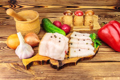 Piece and sliced fresh, raw pork lard on wooden board with vegetables, spices on the table. Piece and sliced fresh, raw pork lard on wooden board with Stock Image