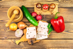 Piece and sliced fresh, raw pork lard on wooden board with vegetables, spices on the table. Piece and sliced fresh, raw pork lard on wooden board with Royalty Free Stock Photos