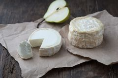 Piece smelly camembert cheese on a wooden rustic table. Brie type of cheese. Camembert cheese. Fresh Brie cheese and a slice on a wooden board with pearand knife royalty free stock image
