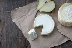 Piece smelly camembert cheese on a wooden rustic table. Brie type of cheese. Camembert cheese. Fresh Brie cheese and a slice on a wooden board with pear and royalty free stock photo