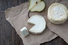 Piece smelly camembert cheese on a wooden rustic table. Brie type of cheese. Camembert cheese. Fresh Brie cheese and a slice on a wooden board with pear and stock image