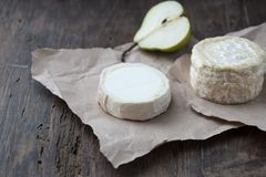 Piece smelly camembert cheese on a wooden rustic table. Brie type of cheese. Camembert cheese. Fresh Brie cheese and a slice on a wooden board with pearand knife stock photos