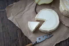 Piece smelly camembert cheese on a wooden rustic table. Brie type of cheese. Camembert cheese. Fresh Brie cheese and a slice on a wooden board with pear and stock photo