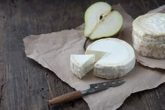 Piece smelly camembert cheese on a wooden rustic table. Brie type of cheese. Camembert cheese. Fresh Brie cheese and a slice on a wooden board with pear and royalty free stock images