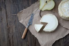 Piece smelly camembert cheese on a wooden rustic table. Brie type of cheese. Camembert cheese. Fresh Brie cheese and a slice on a wooden board with pear and royalty free stock photos