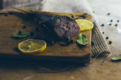 A piece of smoked fish with lemons on the wooden board and hessian cloth. A cut piece of smoked fish with lemons pieces and bay leaves with peppers on the wooden royalty free stock photo