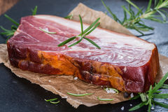 Piece of smoked Ham. (with some fresh herbs) on wooden background Royalty Free Stock Photos