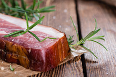 Piece of smoked Ham. (with some fresh herbs) on wooden background Stock Image