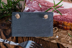 Piece of smoked Ham. (with some fresh herbs) on wooden background Stock Photography
