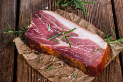Piece of smoked Ham. (with some fresh herbs) on wooden background Royalty Free Stock Photo