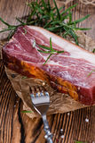Piece of smoked Ham. (with some fresh herbs) on wooden background Royalty Free Stock Image