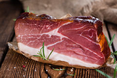 Piece of smoked Ham. (with some fresh herbs) on wooden background Stock Photos