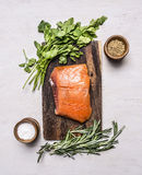 Piece of smoked salmon on a cutting board with herbs spices on wooden rustic background top view Stock Photo